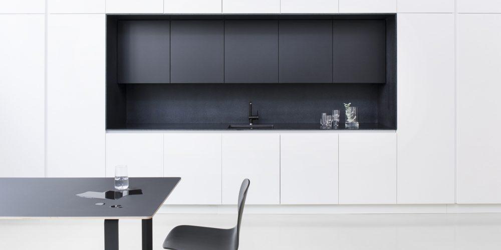 Mattapintainen mustavalkoinen keittiö ja ruokailutila.