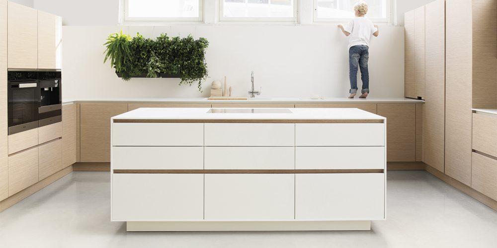 Poika seisoo työtason päällä vaaleassa keittiössä.
